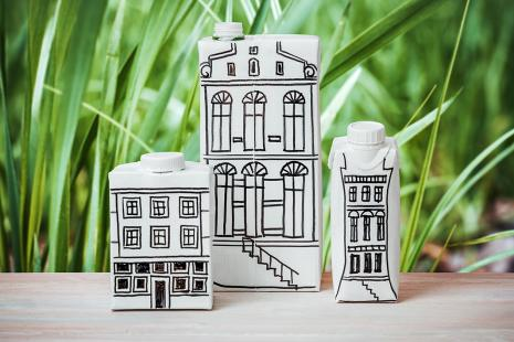 Upclycle art milk containers with buildings drawings in black background green grass
